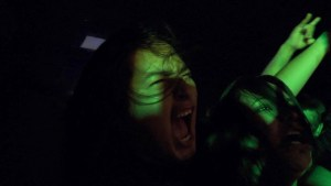"""A young person's screaming face is barely visible in a dark space with green light. A young woman's face can also be seen smiling. Another person's arm is holding up a """"horns"""" hand gesture."""