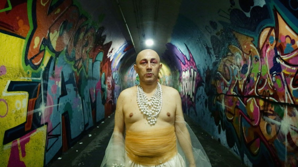 A transgender individual wearing necklaces and a yellow skirt standing in a tunnel with graffiti.