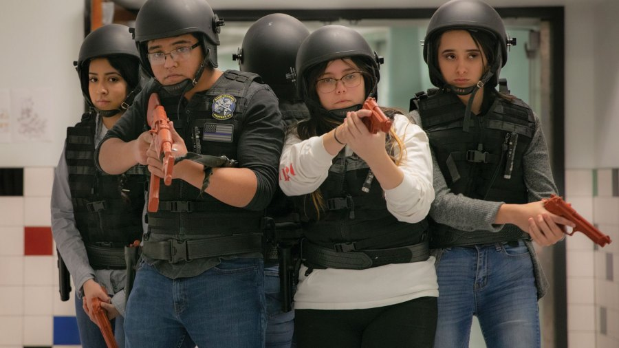 A group of students are wearing helmets, orange guns, and vests.