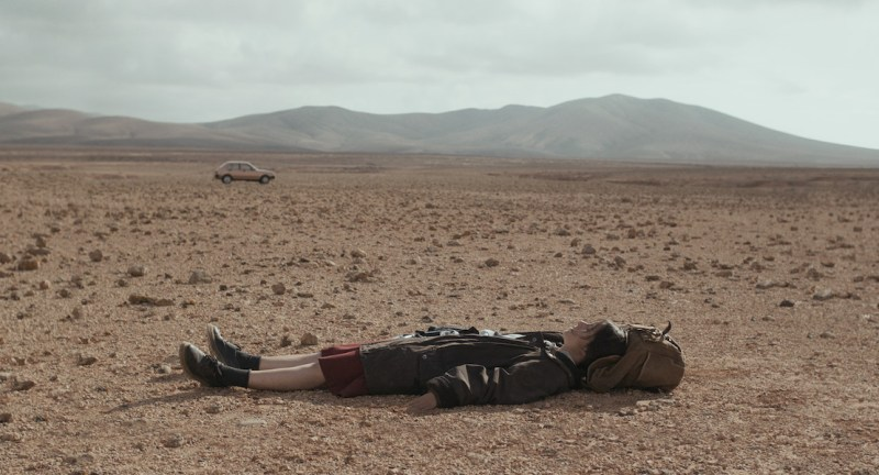 Woman lays on an empty desert landscape.