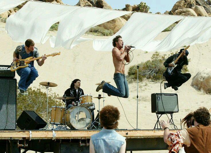 El video Show me how to live intercala escenas de persecusión con un show en medio del desierto