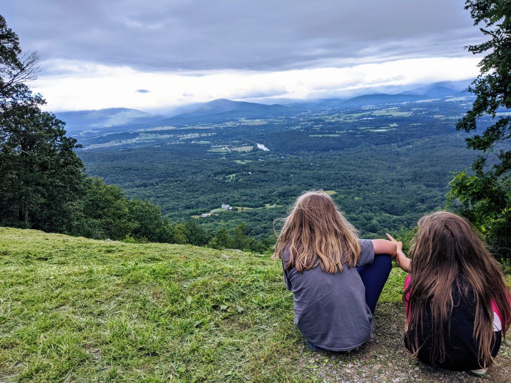 Petra and Silas seen from behind, looking down over the Shenandoah Valley from a high vantage point.
