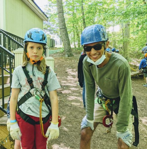 Silas and Carlos in high ropes gear. Carlos is grinning, and Silas looks perturbed.
