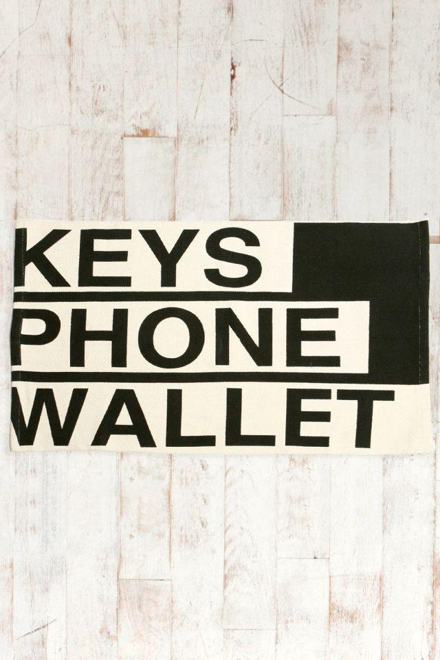 """Capacho com os dizeres """"keys, phone, wallet"""" (""""chaves, celular, carteira"""") da Urban Outfitters."""