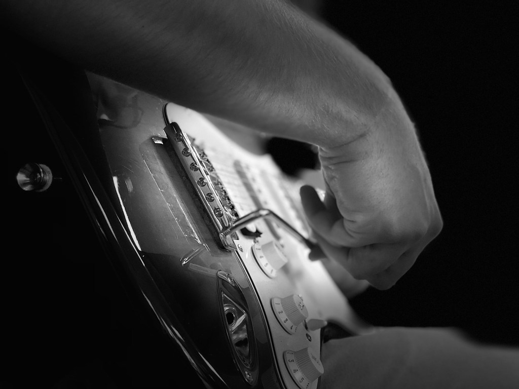 Close-up side view of person playing electric guitar