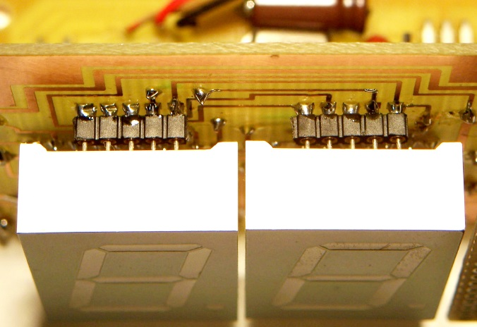 The seven-segment LED displays were mounted on the foil side of a single-sided circuit board. I used single-row, in-line sockets to facilitate soldering. The sockets also elevated the displays above the circuit board and the SMT resistors placed beneath the displays.