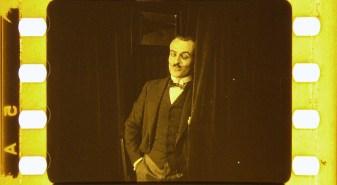 A man listens from behind a curtain.