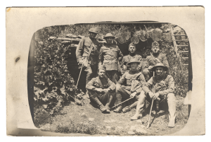 a group of solders in uniform pose outside.