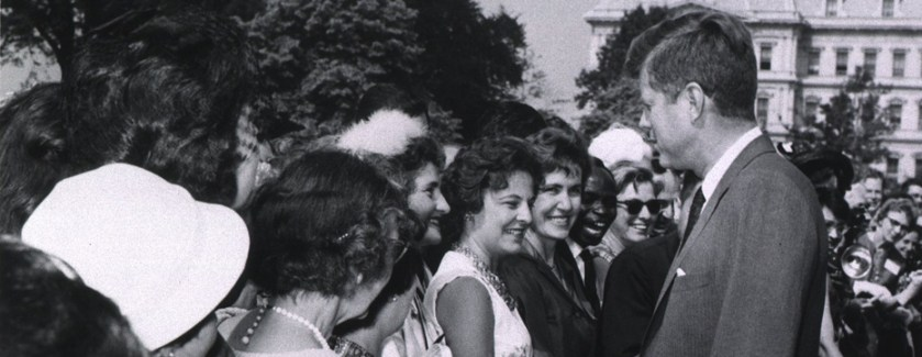 President Kennedy personally greeting a woman in a large crowd of people.