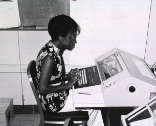 A woman works at a machine resembling a very large electric typewriter.