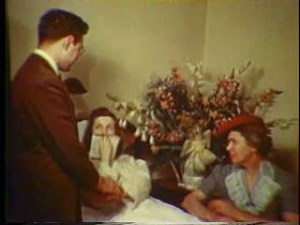 A young woman, covering her mouth, lies in bed. A young man and older woman attend her. Flowers decorate the room.