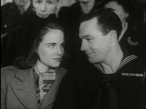 Gene Kelly as Seaman Bob Lucas in uniform smiling at Jocelyn Brando who plays his fiancee Sue.