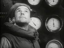Gene Kelly as Seaman Bob Lucas wearing a life vest and sailor hat gazes upward, a panel of gauges display behind him.