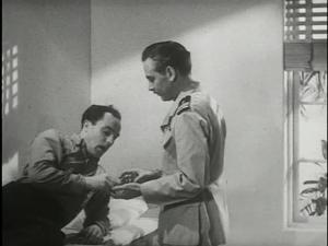 Lauren Gilbert, who plays amilitary psychiatrist, gives medicine to Gene Kelly playing Seaman Bob Lucas.