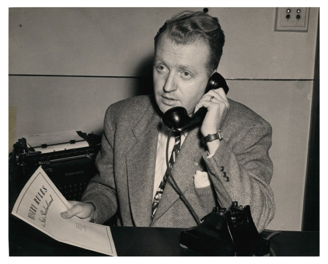 A young man in a suit holding a document talks on the phone.