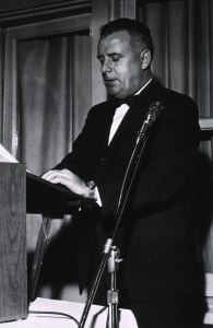 A man in a tuxedo stands at a podium.