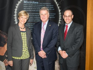 """Three people in business clothes pose in front of a banner that is headed """"Microbes"""""""