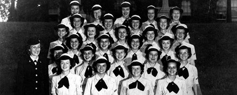 A group of about 30 women pose in uniform.