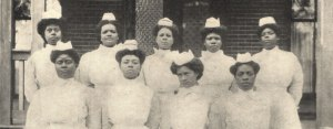 Nine black women in white uniforms with caps pose in rows on the steps of a building.