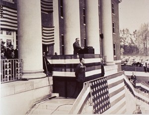 President Roosevelt stands at a podium surrounded by american flags at the top of the steps of a colonial brick building.