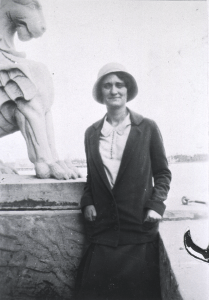A white woman in a cloche hat and overcoat poses by a statue.