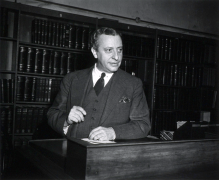 John F. Fulton standing in a library.