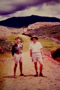 Two men in shorts stand on a dirt road with low mountains in the background.