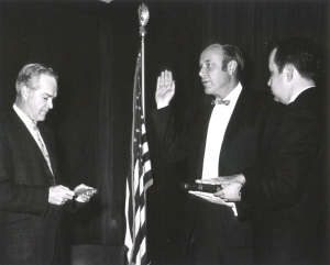 Chalmers stands by an American flag with one hand on a book and the other raised for an oath.