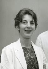 A young woman in a white lab coat.