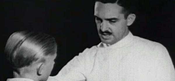 A dentist puts his hand on a boy's shoulder.