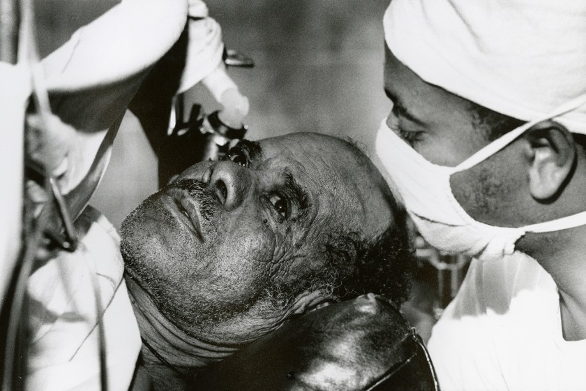 a doctor in a surgical mask leans over a patient's face in surgery.