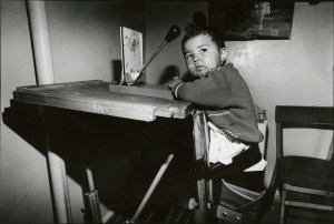 A small child sits in a supportive chair at a table.