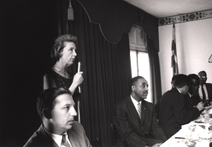 A woman addresses an audience from a microphone positioned behind a table at which sits a group of men.