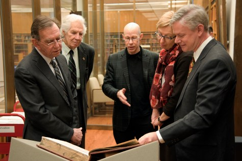 Five people stand around an open book in the NLM's reading room.