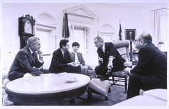 In a group seated around a coffe table, President Johnson leans forward to speak to Nirenberg.