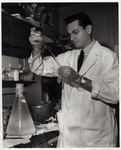 Nirenberg in the lab in a lab coat and gloves manipulating glassware.