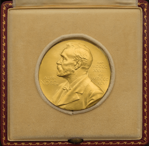 A golden medal featuring a profile portrait of Alfred Nobel in a presentation case.