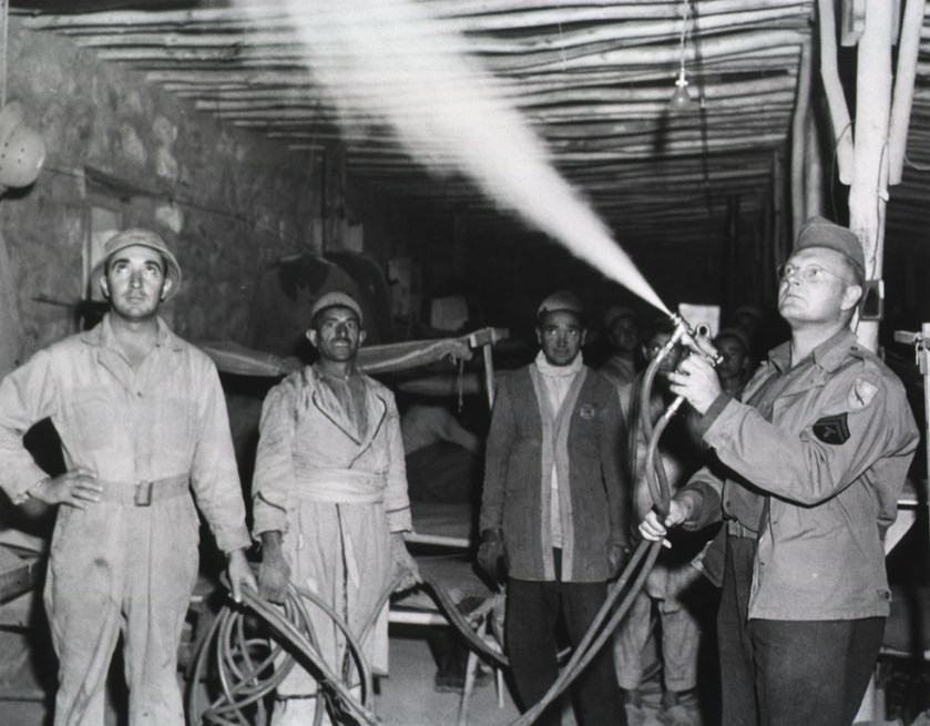 Spraying enlisted men's barracks with DDT