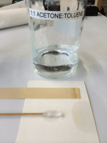 A bottle of clear liquid labeled 1:1 Acetone:Toluene, a cotton swab and a test strip of paper.