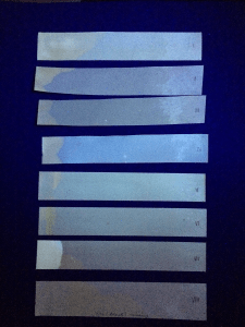 The test strips under ultraviolate light, here the oil saturated sections look brighter.
