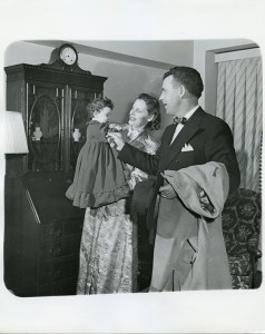 In a living room, a man holding a coat and hat reaches out to a small child held by a woman.