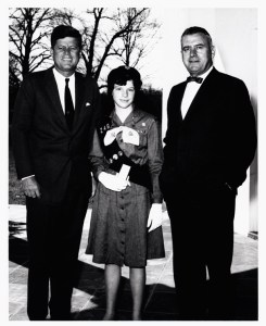 Mary, in a girl scout uniform, stands on a patio between her father and President Kennedy.