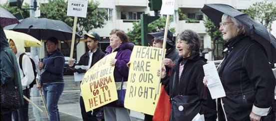 Demonstrators hold signs.