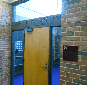 "A door in a brick building with a brass sign over it reading ""John E Fogarty Room Special Collections."""