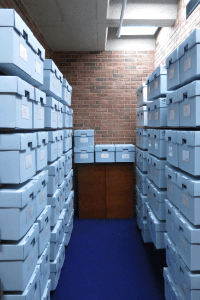 A narrow brick room stacked floor to celing with archival boxes.