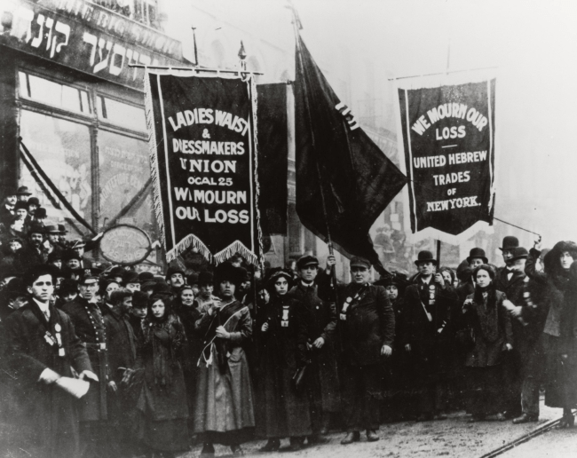 Men and women demonstrate holding banners.