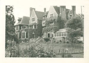 A very large manor house with ivy on the walls and a lawn and gardens.