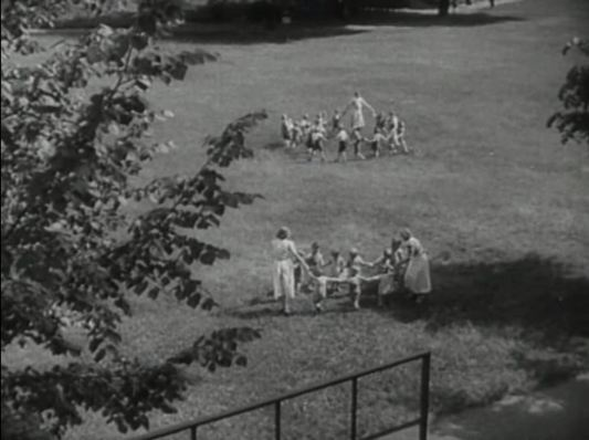 an ariel view of children playing circle games on a lawn.