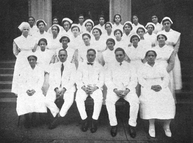 33 African American male and female doctors and nurses gathered for a group photograph.