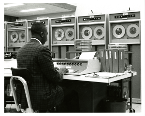 A man sits at a keyboard in a room full of reel to reel machines.